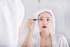 Donna che guarda specchio e trucco con l'eye-liner nero Immagine Stock
