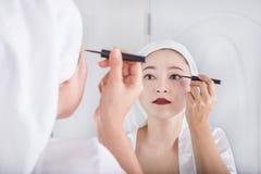Donna che guarda specchio e trucco con l'eye-liner nero Immagine Stock Libera da Diritti