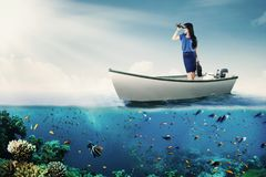 Donna che guarda tramite il binocolo sulla barca Fotografia Stock Libera da Diritti