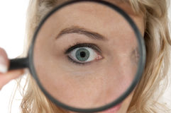 Donna che guarda tramite una lente d'ingrandimento con il grande occhio Fotografia Stock