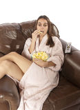 Donna che guarda TV e che mangia popcorn Immagini Stock