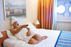 Donna che guarda TV sul suo letto Immagine Stock