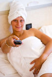 Donna che guarda TV sul suo letto Fotografie Stock