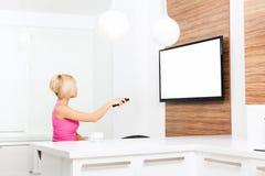 Donna che guarda TV tenere telecomando immagine stock