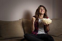 Donna che guarda un gioco sulla TV e sull'incoraggiare fotografia stock