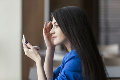 Donna che guarda in un piccolo specchio in ufficio fotografia stock