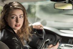 Donna che guida e che manda un sms Fotografia Stock