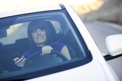 Donna che guida tenendo un cellulare immagini stock