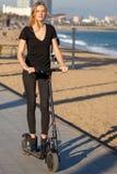 Donna che guida un motorino elettrico in vacanza immagini stock