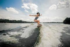 Donna che guida wakeboard rosa alla moda sull'alta onda Fotografia Stock Libera da Diritti