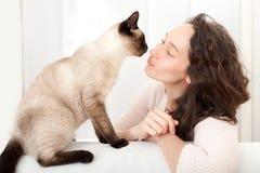 Donna che ha buoni periodi a casa con il gatto fotografia stock
