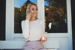 Donna che ha conversazione piacevole sul telefono delle cellule durante il pranzo in caffè del marciapiede Immagine Stock