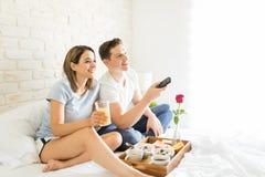 Donna che ha Juice By Boyfriend Changing Channels sul letto immagini stock libere da diritti
