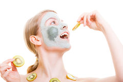 Donna che ha maschera del fango sul kiwi della tenuta del fronte Immagini Stock Libere da Diritti