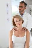 Donna che ha massaggio della spalla dal chiropratico Fotografia Stock