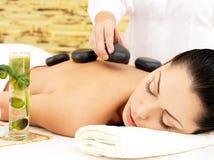 Donna che ha massaggio di pietra caldo della parte posteriore nel salone della stazione termale Immagini Stock