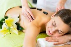 Donna che ha massaggio di pietra caldo di benessere Fotografie Stock Libere da Diritti