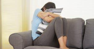 Donna che ha un mal di stomaco e che abbraccia cuscino Immagini Stock Libere da Diritti