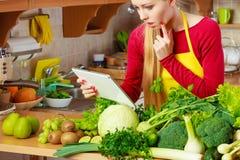 Donna che ha verdure verdi che pensano alla cottura Immagine Stock