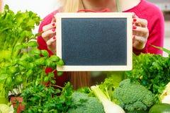Donna che ha verdure verdi che tengono bordo Immagine Stock