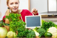 Donna che ha verdure verdi che tengono bordo Immagine Stock Libera da Diritti