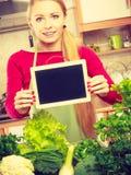 Donna che ha verdure verdi che tengono bordo Immagini Stock