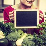 Donna che ha verdure verdi che tengono bordo Fotografie Stock Libere da Diritti