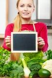 Donna che ha verdure verdi che tengono bordo Immagini Stock Libere da Diritti