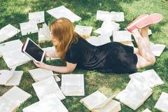 Donna che impara con il lettore ed il libro del libro elettronico Scelta fra tecnologia educativa moderna ed il metodo tradiziona Immagini Stock Libere da Diritti