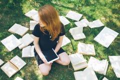 Donna che impara con il lettore ed il libro del libro elettronico Scelta fra tecnologia educativa moderna ed il metodo tradiziona Immagine Stock