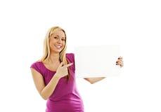 Donna che indica al segno della carta in bianco con lo spazio della copia Fotografia Stock Libera da Diritti