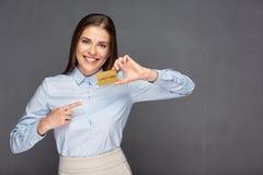 Donna che indica dito alla carta di credito dell'oro Fotografia Stock