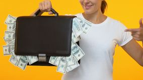 Donna che indica dito nella cartella in pieno di soldi, servizio di credito di attività bancarie stock footage