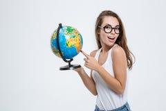 Donna che indica dito sul globo e che esamina macchina fotografica Fotografia Stock Libera da Diritti