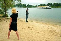 Donna che indica pistola all'uomo Fotografie Stock