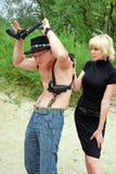Donna che indica pistola all'uomo di cessione Fotografia Stock Libera da Diritti