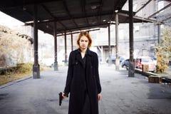 Donna che indica una pistola Fucilazione della ragazza della mafia a qualcuno sulla via Fotografie Stock
