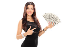 Donna che indica verso una pila di soldi Fotografia Stock Libera da Diritti