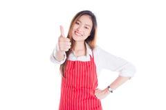 Donna che indossa grembiule rosso, sorridente e mostrante pollice su Immagini Stock