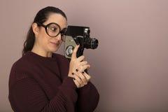 Donna che indossa i grandi vetri facendo uso della macchina fotografica d'annata Immagini Stock Libere da Diritti