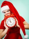 Donna che indossa l'orologio della tenuta del costume di Santa Claus Immagine Stock
