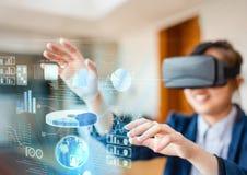 Donna che indossa la cuffia avricolare di realtà virtuale di VR con l'interfaccia Fotografia Stock