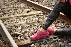 Donna che indossa le scarpe rosa alla stazione ferroviaria Immagini Stock
