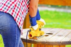 Donna che insabbia una tavola di legno con una sabbiatrice elettrica gialla Fotografia Stock