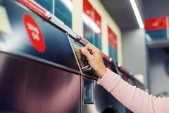 Donna che inserisce moneta in primo piano della lavatrice di self service Immagine Stock Libera da Diritti