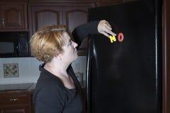 Donna che invia NO per la motivazione stante a dieta sul frigorifero Fotografia Stock
