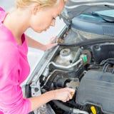 Donna che ispeziona il motore di automobile tagliato Fotografia Stock Libera da Diritti