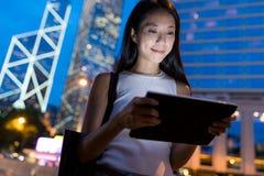Donna che lavora al computer della compressa alla notte Immagini Stock