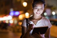 Donna che lavora al computer digitale della compressa alla notte Fotografia Stock