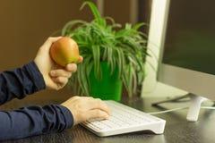 Donna che lavora al computer e che tiene una mela fotografia stock